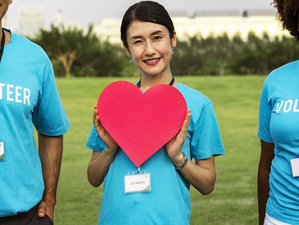 Volunteer holds paper heart
